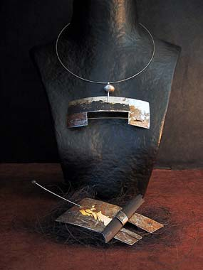 Necklace and brooch: recycled metal oxidized patinated with gold leaf