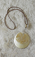 Necklace: big mother of pearl disc, gold foil, leather string