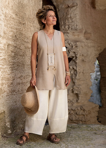 Safari style: sleeveless beige linen tunic and linen trousers.
